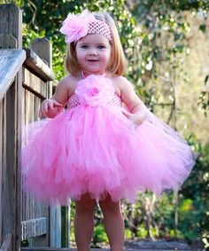 Help any little ballerina look the part with this lovely tutu dress and matching headband. The frock features a frilly tulle skirt and a stretchy halter top with a big, pretty blossom.