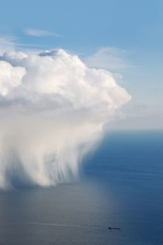 A lone cargo ship emerges from an ocean rain cloud formation.