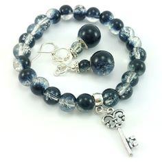 Komplet biżuteriidamskiej wykonany ręcznie. Kolczyki i bransoletkaz czarnych koralików szklanych i elementów w kolorze srebrnym. Dodatkowo zawieszka charms w kształcieklucza (akryl).