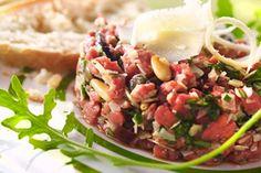 Recept voor: rundertartaar op italiaanse wijze   1. Rooster de pijnboompitten zonder vetstof in een pan met antikleefbodem. 2. Snij enkele schilfers van de blok parmezaan en rasp de rest van de kaas met de grove kant van de rasp. Hak de olijven en de helft van de  …