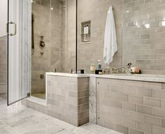 Gray brick-like tile in the bathroom compliments the gray and white marble floors