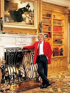 Rod Stewart standing by his fabulous fire place. That iron work is very nice.