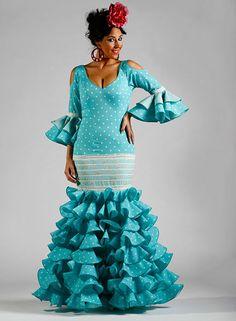 Traje de flamenca Fantasía de color turquesa con lunares blancos de talle bajo con ocho volantes y mangas a los codos con volantes. Cuello de pico.
