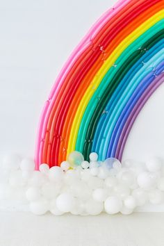 Your next party needs this DIY rainbow balloon backdrop for your photo booth.