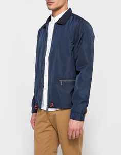 From Native Youth, a modern coaches jacket in Navy tech fabric. Featuring a point collar in navy knit, full length sleeves, elasticized cuffs, underarm grommet vents, a full length two way zip closure, branded pull tabs in a neutral gunmetal shade, two to