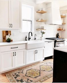 Adore the aesthetic! Natural wood shelves, farmhouse sink, all white cabinets and bench tops, cute decor and a beautiful rug! Only thing I don't like is the black island. Would prefer if it was natural wood or white wood.