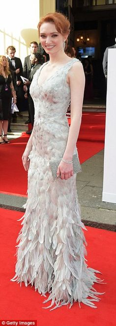Making a statement: Poldark star Eleanor Tomlinson (centre) chose an unusual dove grey gown from Ralph Lauren which was made up of hundreds of feathers
