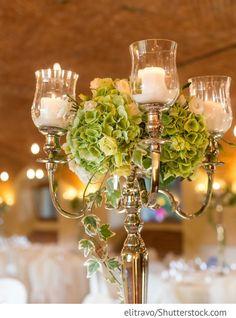 Kerzenständer auf den Hochzeitstischen mit Hortensien, Rosen und Efeu für russische Hochzeiten