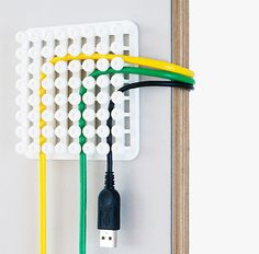 Poketo Cable Organizer. This cable organizer securely holds a wide-range of wires between its grid of flexible knobs, making it easier to organize the wires & power supplies in your office-space. Poketo's adhesive back allows the organizer to attach easily to any clean surface, making it easy to find the cords you need when you need them.