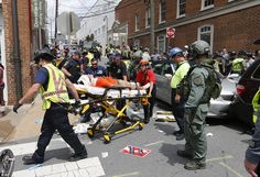 Rescue personnel help an injured man after the car drove into a large group of protesters after the white nationalist rally in Charlottesville
