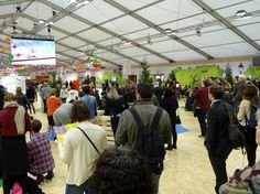 """COP21 visitors in the """"green zone"""" where various exhibits, presentations and informal gatherings took place in Paris. Some presentations from the """"blue zone,"""" where U.N. members and world leaders gathered to discuss climate change legislation, were displays on video monitors in the """"green zone."""" Photo by Brian Kaylor."""