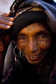 Fulani ( Peul ) woman on Birni Kazoe market, eastern Niger. Fulani are nomad tribe spread all over West Africa Sahel belt, they travel a lot and seem to be a lot more open and intelligent than settled folk.They are dreamers, storytellers and singers, and they have great sense of humour.