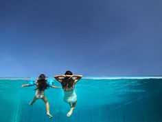 Picture of a mother and daughter relaxing in a clear-walled swimming pool, Bali, Indonesia