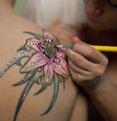 This is a cool idea. Decorating your tattoo for your wedding.  I have tattoos and I didn't cover them for my wedding. If you feel that you need to cover your tattoo for your wedding, maybe you shouldn't have gotten a tattoo in the first place. If you are having a religious ceremony, wear something that covers the tattoo. My friend got married in a Catholic Church and had a lace jacket, it covered her back tattoo.
