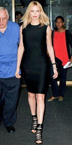 Look of the Day › May 30, 2012 WHAT SHE WORE Theron exited N.Y.C.'s Rockefeller Center in a knee-length LBD, sleek J/Hadley bangles and strappy Christian Louboutin heels.