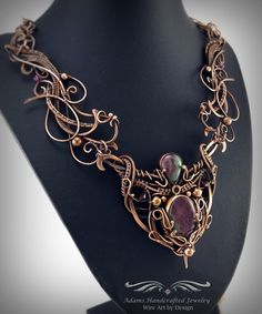 Regalia -- Once Upon a Time **2016 Nicole Hanna Design Challenge Winner Mixed Media** Ruby in Zoisite gemstones wire-wrapped necklace in an antiqued copper finish adorned w/ crystal accents. Make a statement with this timeless exquisite piece! Loving & careful attention were given to every f