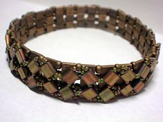 "Tumbling Miyuki Tila Beads woven together with Toho Seed Beads.    Base of Bangle ~ Matte Metallic Tila Beads and 6/0 Matte Dark Bronze Seed Beads  Tumbling Tilas ~ Opaque Matte Olive Rose  Woven Seed Beads ~ 15/0 Opaque Golden Olive Luster    Bangle measures 3/8"" in width and fits up to 9"" diameter."