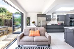 Single-storey kitchen extension to 1930s house in Long Ditton by L&E (Lofts and Extensions) - don't move extend. Grey Kitchen, Glossy Kitchen, Skylights, Patterned Tiles, Bi-Fold Doors