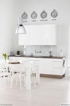 valkoinen keittiö,valkoinen,välitila,keittiön välitila,keittiönkaapit,ruokapöytä,ruokailuryhmä,kello,teksti,keittiö,avokeittiö