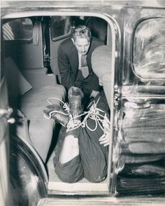 "Trussed from head to foot, the body of Samuel Silverman is examined by Deputy Medical Examiner Romeo Auerbach. The victim was found in a car parked in Brooklyn, N.Y. with three bullets in his skull. Police believe Silverman was killed for ""putting the finger"" on other men involved in a hold up, for which he was out on bail.  July 16, 1937."