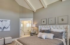 A master bedroom with an on-suite bathroom; a cool, neutral color palette; and tufted bed frame. What do you think of the color scheme? Design by http://www.clayconstruction.ca/