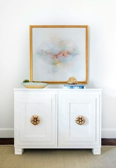 Sophisticated living room features a white cabinets adorned with gold flower knobs under a pastel colored abstract art piece framed in a gold leaf frame. Sophisticated Living Rooms, Transitional Living Rooms, Interior Design New Orleans, Furniture Decor, Painted Furniture, Pastel Interior, Foyer Design, Elements Of Design, White Cabinets
