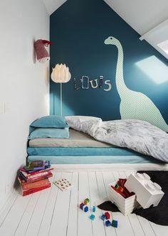 Peindre une petite chambre en blanc pour la faire paraître plus grande et lumineuse, vous connaissez déjà ! Ici, on est carrément allé jusqu'à peindre le vieux parquet ainsi que le plafond et les poutres apparentes des combles en blanc. Le mur du fond est peint dans un bleu canard et décoré d'un adorable dinosaure découpé dans du papier peint. Voilà une idée d'aménagement de combles pour créer une nouvelle chambre lorsque un enfant est en âge de prendre un peu d'indépendance