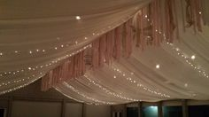 The ceiling fully covered with sheer white fabric that was accented with twinkle lights.  Completed with long strands of hanging ribbon. #sugarsnapevents #sanderlingresort