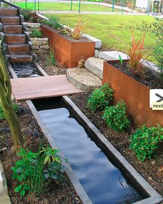 Two level rill with stepped waterfall takes advantage of the slope, with planters serving as retaining walls.