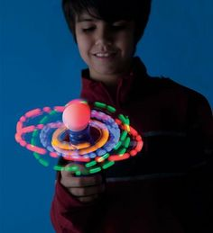 """Hand-Held LED Galaxy Spinner with Flashing LED Lights by Windy City Novelties®. $7.99. Our Galaxy Spinner with flashing LED lights is out of this world! Kids will love to light up the night with this hand-held spinner that glows and spins at the same time. Requires 3 AAA batteries (included). Size: 8"""" diam. For ages 6 and up."""