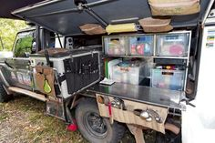 Camper Kitchen. Food use of plastic boxes for storage and a pull our stove and work bench