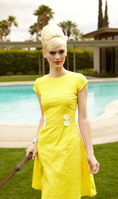 Whether mowing the lawn or going to a garden party, this yellow frock is made for the sunshine.  Bold white buttons adorn the waist and an A-line skirt gracefully descends from the waist of this sophisticated shift. The crisp cotton, woven fabric combines both comfort and chic.  .   The dress is completed with cute cap sleeves and a side zipper.