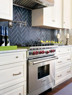 A slate-colored tile backsplash paired with stainless steel appliances gives this kitchen an updated traditional look. The white cabinetry adds dimension and contrast to the space.