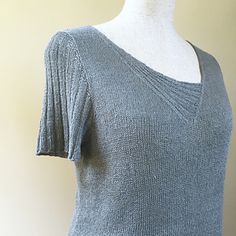 Sel Gris features an asymmetrical V-neck with ribbed details and matching ribbed sleeves. The ribbed part of the neckline is worked with the right front after having picked up additional stitches at the left neckline.