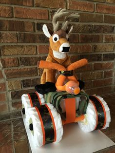 Diaper Camo 4-wheeler diaper cake.  48 Pampers Swaddlers size 2, 1 pkg. Pampers Sensitive Wipes, 1 orange Nuby bottle, 1 Camo receiving blanket, 2 pr. Black baby socks size 6-18 mos, 5 orange washcloths, 2 brown washcloths, 1 plush deer, orange and camo ribbon, cardstock.