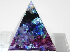 Item size: 3,5x3,5x4cm and it weights approx 30 gr   I use transparent epoxy resin that is glass like and very durable and makes the colors really pop.  This resin pyramid is beautifully faceted and reflects the light in a lovely way. The holographic flakes seem to give it a glow from within. The colors go from purple to blue over black to transparent white and has iridescent, holographic flakes that shimmer in all rainbow colors.  Each item is unique and crafted with care and attention to…