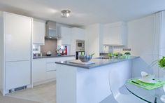 Kuchnia utrzymana w jasnej tonacji: białe fronty mebli, jasno szare blaty i dodatki w delikatnej, wiosennej zieleni.