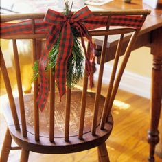 A simple bow tied with patterned ribbon brings a nice Christmas touch to your everyday chair. Tuck in a sprig of greenery to add that classic Christmas tree scent.   No evergreens? Use artificial evergreens or mistletoe to decorate your chairs.