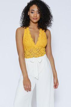 c0766def0 Sleeveless sheer crochet lace bodysuit featuring low surplice neck