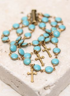 Bronze and turquoise are a winning combination on this multi-strand bracelet. Oval enamel beads link along three lengths of chain and slip together with a magnetic bar clasp. Finished with dangling bronze cross charms, this bracelet exudes vintage character. Assurance. #Christian #bling #bracelet #summertime