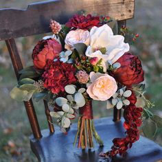 This bouquet is romantic inspired bouquet is made with marsala burgundy peonies, dahlias, magnolia flowers, berries, eucalyptus with wisteria trailing. This bouquet measures 13 wide with greenery extending out further by 15 tall. Matching wedding party flowers are available upon