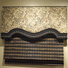 Shaped cornice with contrast banding at the bottom with nail heads. We have made this cornice from a variety of fabric and nail heads here in the store to change up the look! http://www.karensfabrics.com/