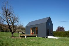 Near the Seine estuary, between woods and orchards, this holiday home appears at first like a dark silhouette, on a green background. It is a simple volume, monochrome, with smooth front, and sharp…