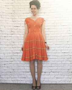 Vintage dress from the 1950s in orange cotton with yellow and green ricrac…
