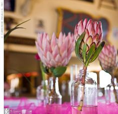 Antique-inspired glass bottles filled with sweet peas, pink ranunculus, and protea decorated each table.