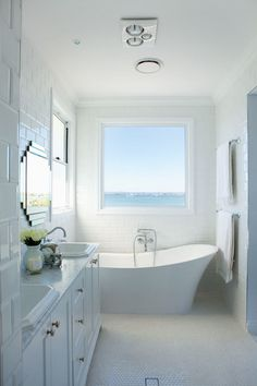 Monochromatic beach bathroom with freestanding tub with wall mounted faucet below large picture window framed by ceiling height beveled subway tile. The bathroom features white penny tiled floors which highlight the white dual sink vanity with nickel hardware accented with white marble counters below art deco vanity mirrors.