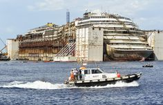 The wreck of the Costa Concordia cruise ship in front of the harbor of Isola del Giglio, Italy,