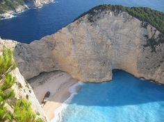 """Navagio Beach or the Shipwreck, is an isolated sandy cove on Zakynthos island and one of the most famous and most photographed beaches in Greece. Navagio Beach is often referred to as the Shipwreck Beach or just simply """"The Shipwreck"""" because it is home to the wreck of a ship called Panagiotis that is believed to have been a smugglers ship. The presence of alleged smugglers ship gave Navagio Beach yet another nick name – Smugglers Cove."""