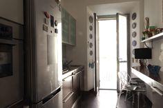 Foto d' insieme del locale cucina. Basi in wengè pensili con ante in vetro, frigorifero esterno in primo piano.