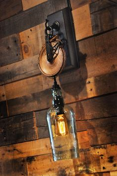 Liquor Bottle Wall Sconce with Pulley by MoonshineLamp on Etsy, $189.00. I like the pulley idea, and wall mounted, not over head hanging